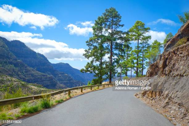 road leading towards mountains against sky - tejeda canary islands stock pictures, royalty-free photos & images