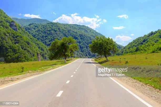 road leading towards mountains against sky - chechnya stock pictures, royalty-free photos & images