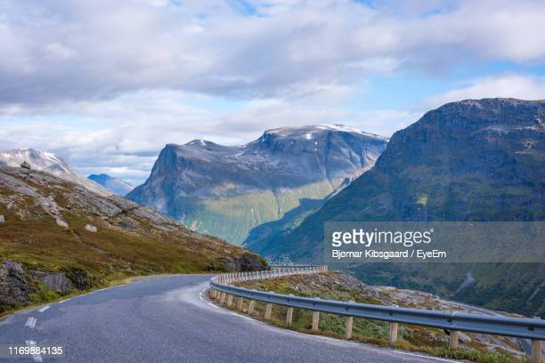 road leading towards mountains against sky - mountain road stock pictures, royalty-free photos & images
