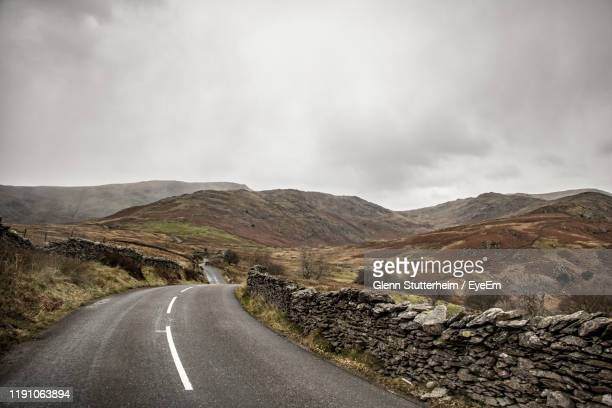 road leading towards mountains against sky - stutterheim stock pictures, royalty-free photos & images