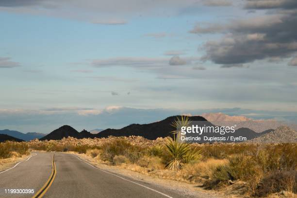 road leading towards mountains against sky - dietlinde duplessis stock pictures, royalty-free photos & images