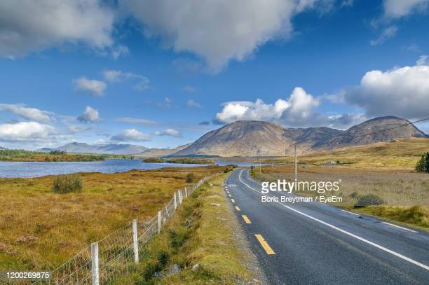 road leading towards mountains against sky - road stock pictures, royalty-free photos & images
