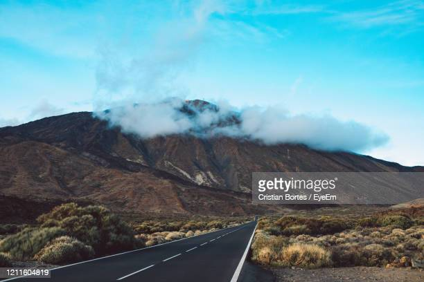 road leading towards mountains against sky - bortes stock pictures, royalty-free photos & images