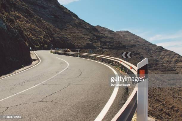 road leading towards mountains against sky - bortes fotografías e imágenes de stock