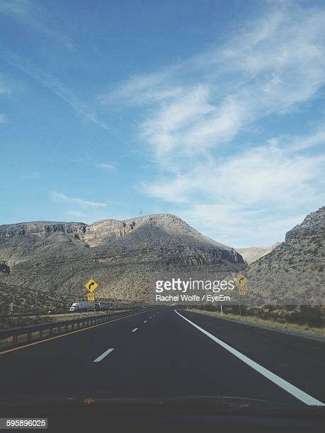 road leading towards mountains against sky - rachel wolfe stock pictures, royalty-free photos & images