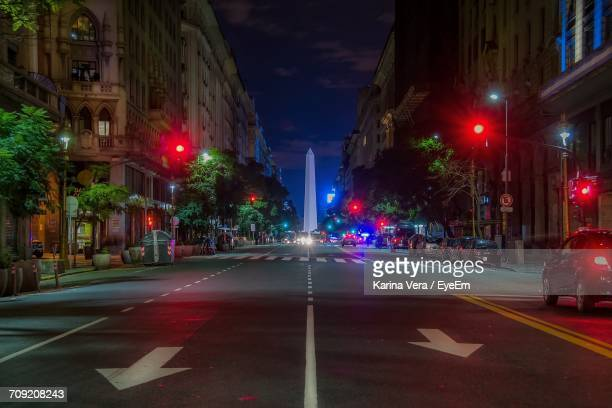 road leading towards obelisco de buenos aires in city at night - obelisco de buenos aires fotografías e imágenes de stock