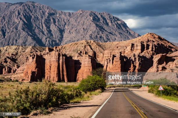 road leading towards rocky mountains against sky - サルタ州 ストックフォトと画像