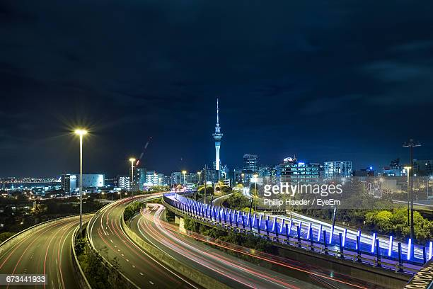 Road Leading Towards Sky Tower Against Sky In Illuminated City At Night