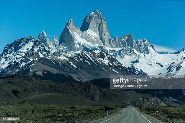 Road Leading Towards Snow Covered Mountains Against Clear Blue Sky