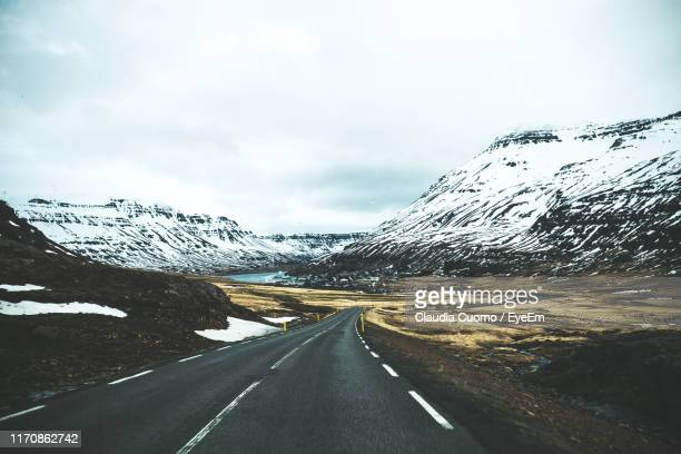 road leading towards snowcapped mountains against sky - cuomo stock pictures, royalty-free photos & images