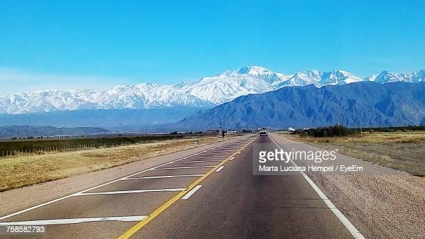 Road Leading Towards Snowcapped Mountains