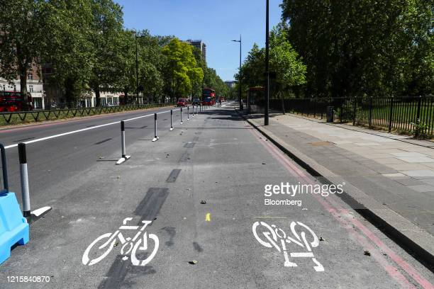 Road markings sit in a new bicycle lane created by Transport for London on Park Lane in London, U.K., on Thursday, May 28, 2020. To get London moving...