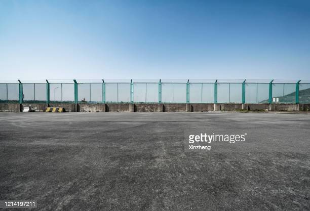 road next to a fence - prison escape stock pictures, royalty-free photos & images
