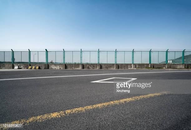 road next to a fence - chainlink fence stock pictures, royalty-free photos & images
