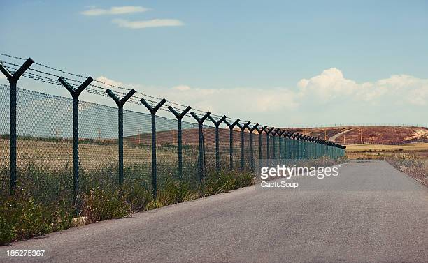 road next to a fence - geographical border stock pictures, royalty-free photos & images