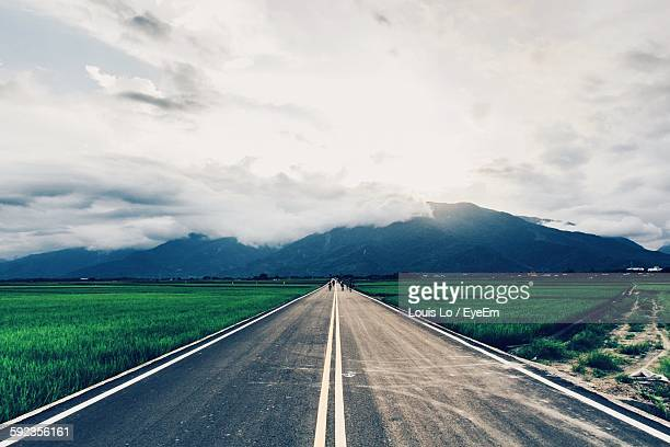 Road On Agricultural Field Leading Towards Mountains Against Sky
