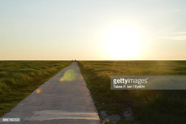 Road On Grassy Field Against Sky During Sunset