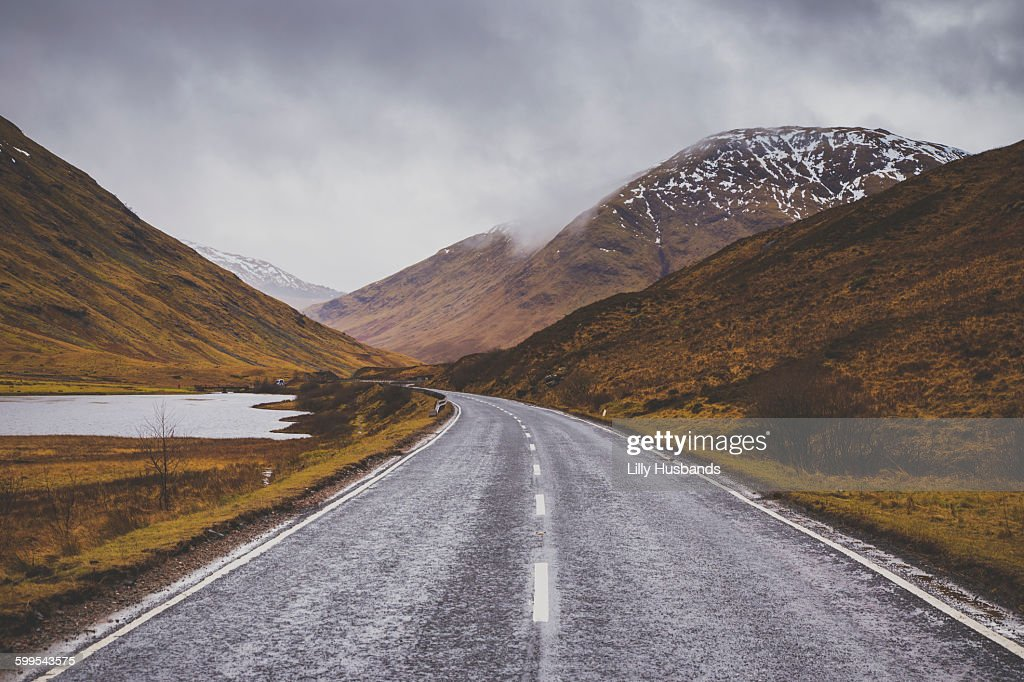 Road passing by mountains against cloudy sky : Stock Photo