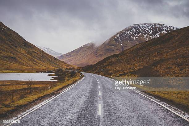 Road passing by mountains against cloudy sky