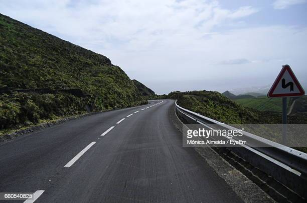 road passing through country landscape against cloudy sky - leitplanke stock-fotos und bilder