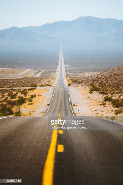 road passing through desert - southwest stock pictures, royalty-free photos & images