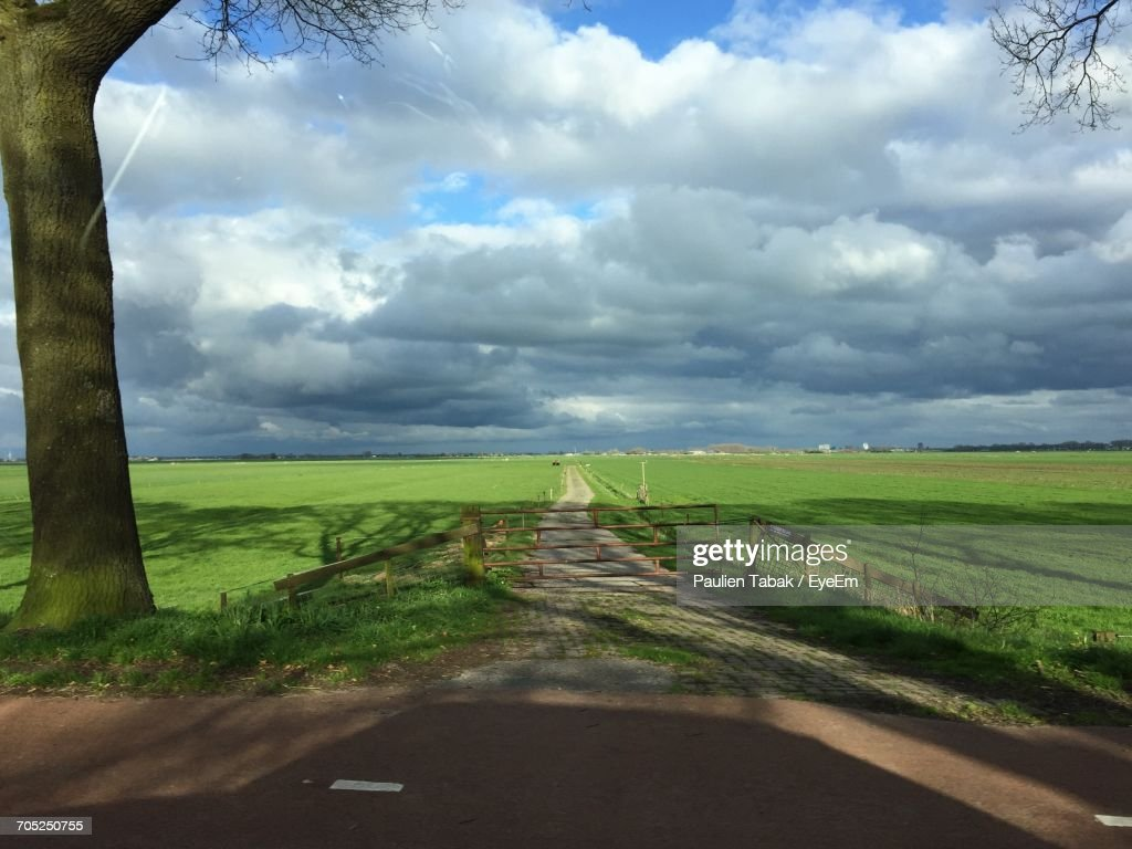 Road Passing Through Field Against Cloudy Sky : Stockfoto