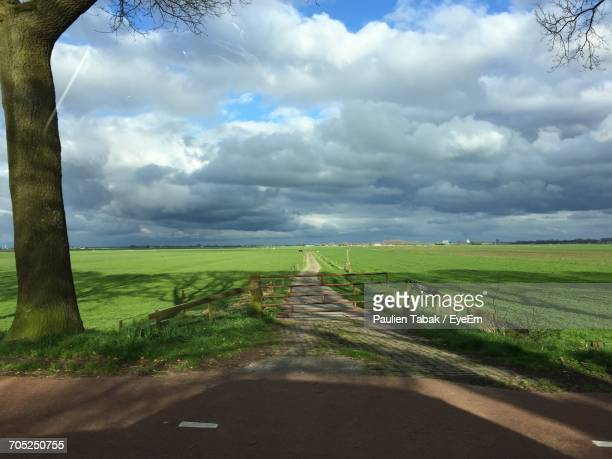 road passing through field against cloudy sky - paulien tabak stock-fotos und bilder