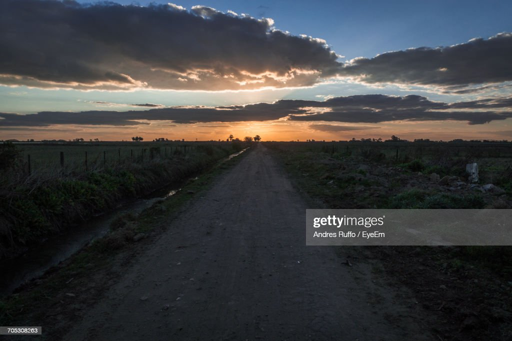 Road Passing Through Field Against Cloudy Sky : Stock Photo