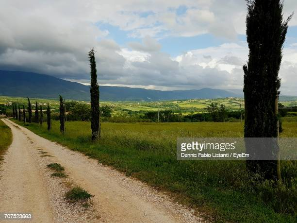 road passing through field against cloudy sky - massa stock pictures, royalty-free photos & images