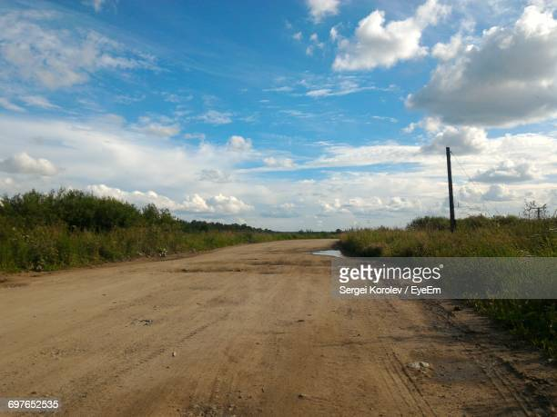 road passing through field - sergei stock pictures, royalty-free photos & images