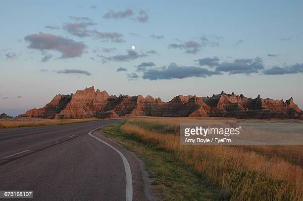 road passing through field towards south dakota badlands - south dakota stock pictures, royalty-free photos & images