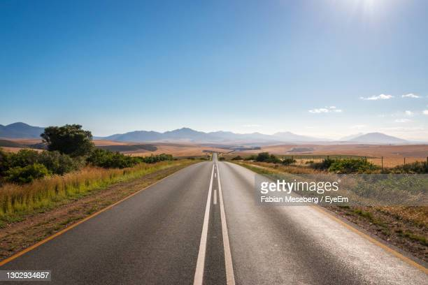 road passing through landscape against sky - overberg stock pictures, royalty-free photos & images
