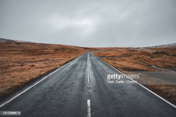 road passing through landscape against sky - remote location stock pictures, royalty-free photos & images