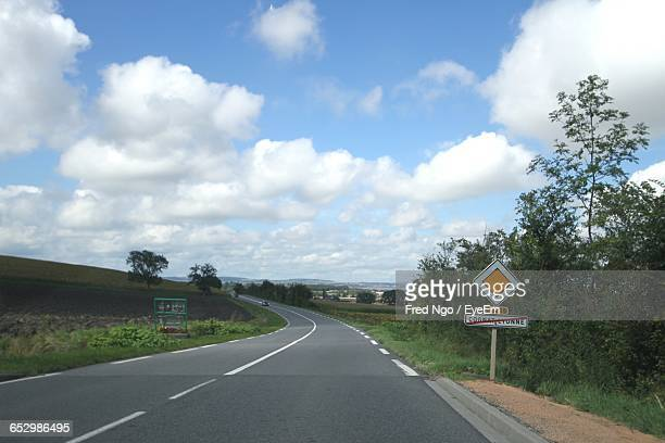 road passing through landscape against sky - allier stock photos and pictures