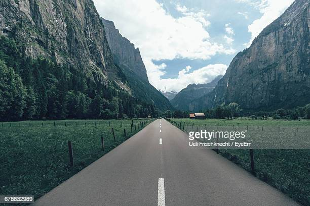 road passing through mountain landscape - fluchtpunkt stock-fotos und bilder
