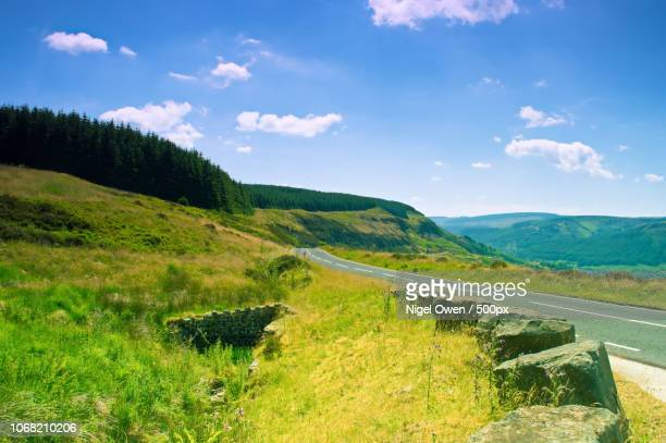 road passing through mountainous landscape - nigel owen stock pictures, royalty-free photos & images
