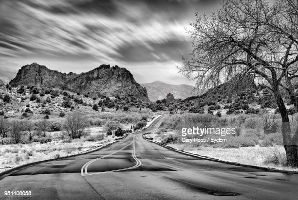 road passing through mountains against sky - garden of the gods stock photos and pictures