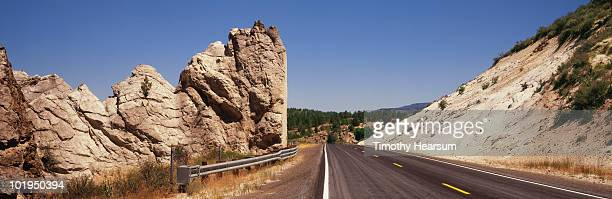 road passing through severe cut in hillside - timothy hearsum stock pictures, royalty-free photos & images