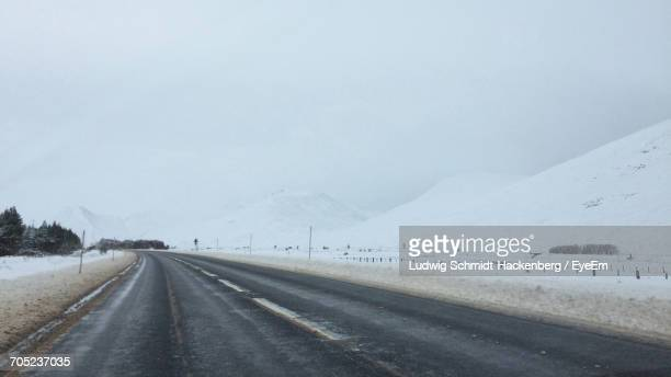 Road Passing Through Snow Covered Mountain