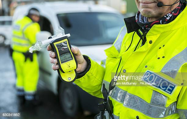 Road Policing officer holds an operational breathalyser during a random drink driving checkpoint in Belfast