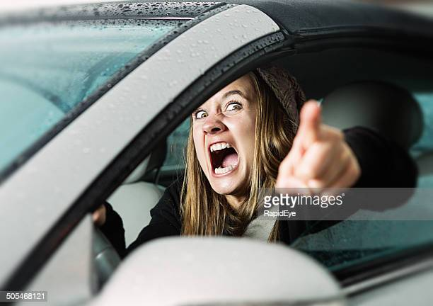 Road rage! Enraged young woman driver shouts and points accusingly.