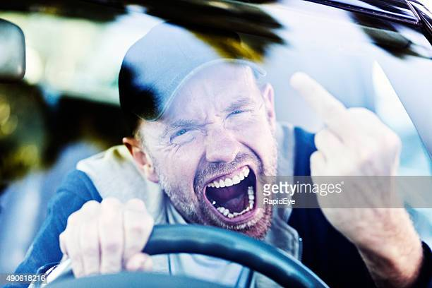 Road rage: furious male driver makes obscene gesture, yelling