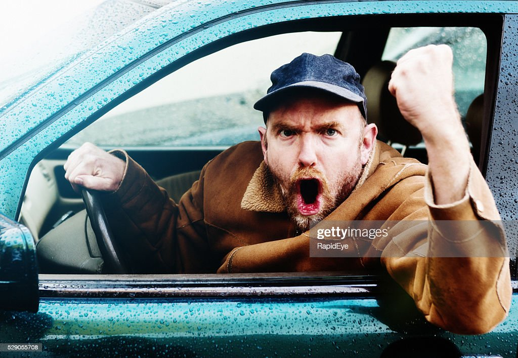 Road rage: Furious male driver yelling, shaking fist through window : Stock Photo