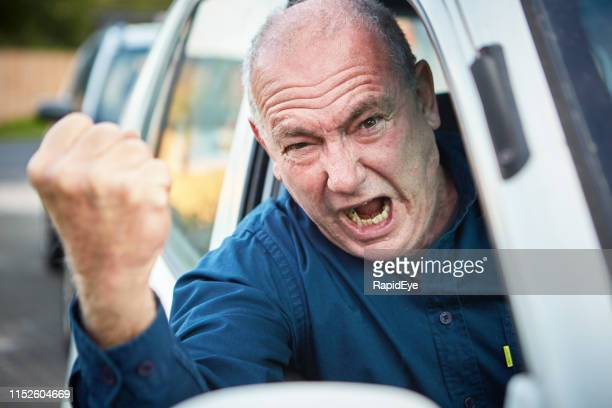 road rage: furious senior male driver shaking fist and shouting - ominous stock pictures, royalty-free photos & images