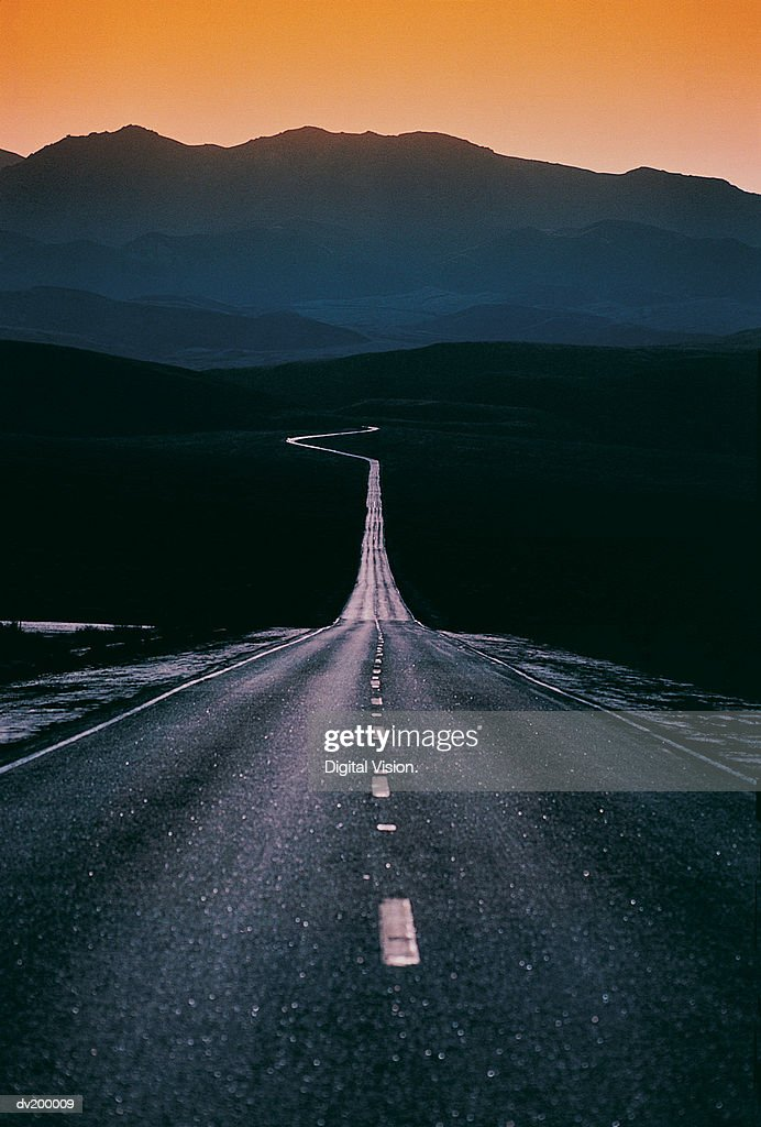 Road reflected against dark mountains : Stock Photo