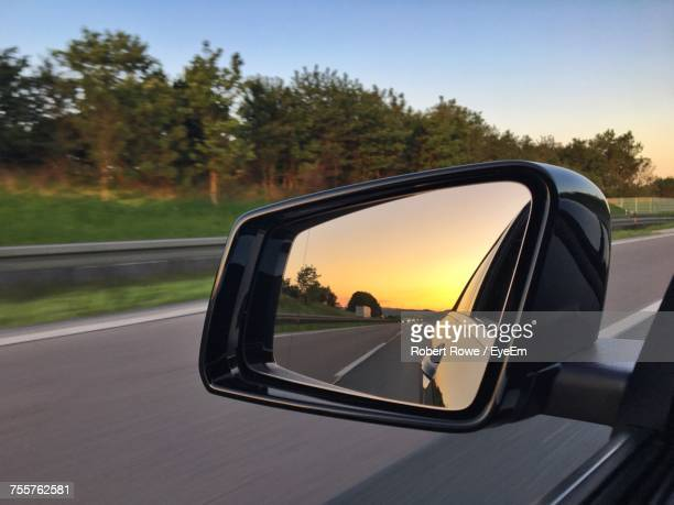 road reflecting on side-view mirror of car during sunset - side view mirror stock photos and pictures