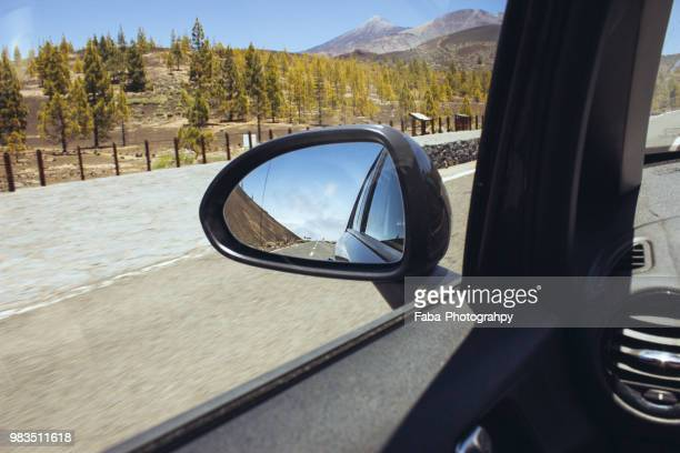 road reflecting on side-view mirror of car - vehicle mirror stock photos and pictures