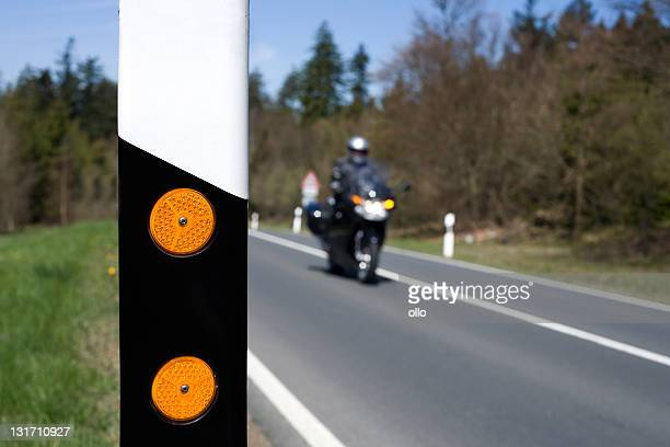 Road reflector and motor-cyclist, selective focus