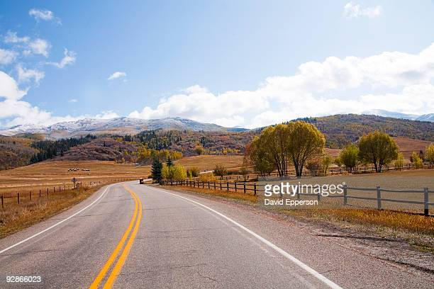 road running thru fall landscape - steamboat springs colorado stock photos and pictures