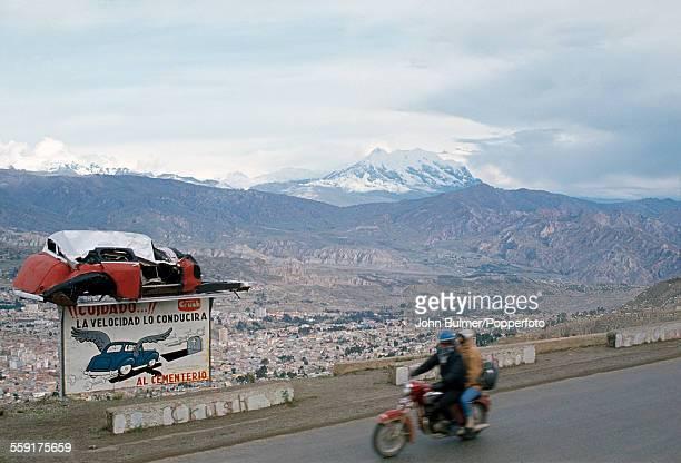 A road safety sign above the city of La Paz in Bolivia circa 1983 It reads 'Cuidado La Velocidad lo conducira al Cementerio'
